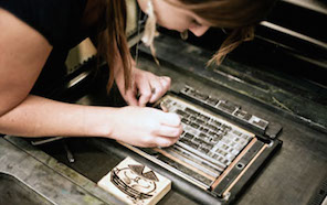 student arranging letters on the press
