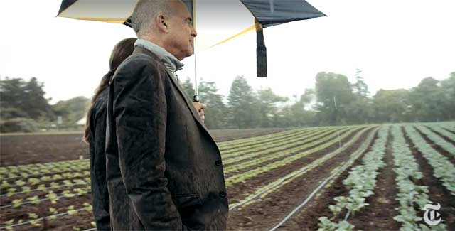 mark bittman under an umbrella with rows of crops at the u c santa cruz farm in the background