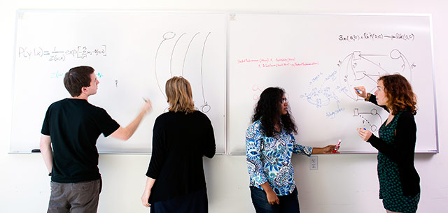 Students drawing on a white board
