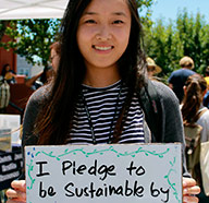 UC Santa Cruz student holding sign I pledge to be sustainable by