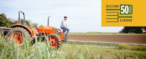 A farmer sits on his tractor next to crops