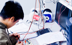 A lab technician works on circuitry.