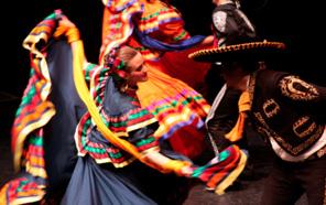 Grupo Folklórico Los Mejicas perform a dance onstage.